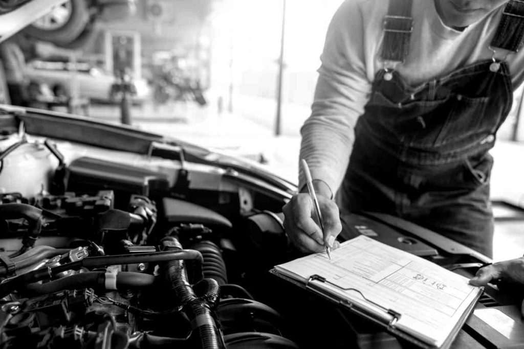 person working on a car engine, checking off items on a list